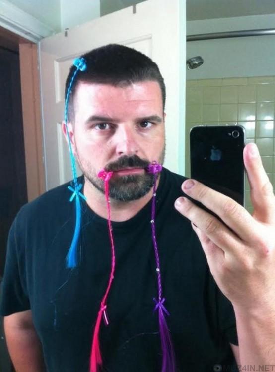 selfi de un hombre frente al espejo con trenzas adornando su barba