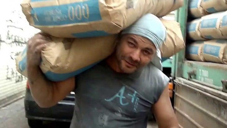 Hombre carga dos bultos de harina
