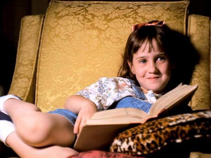 Actriz de la película Matilda leyendo en sofá