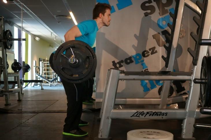 Levantar peso en barra, en posición encorvada