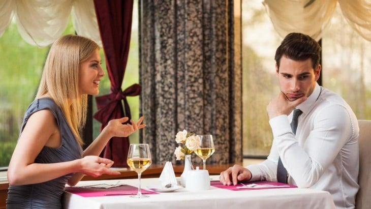 Hombre aburrido en una cita con una rubia