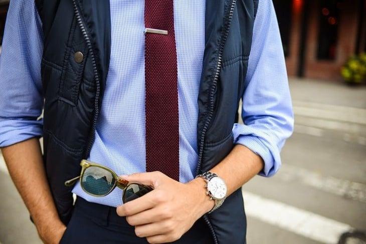 Con corbata y chaleco y lentes en la mano