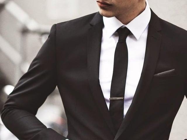 Traje negro con corbata delgada y negra