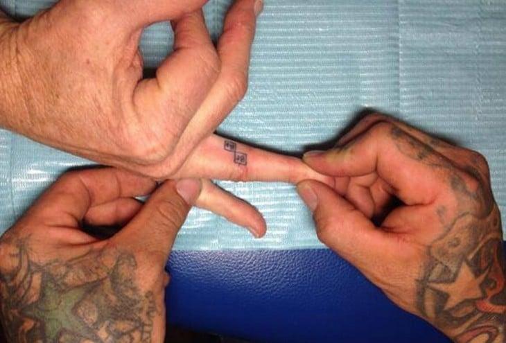tatuaje del logo de Breaking Bad en un dedo