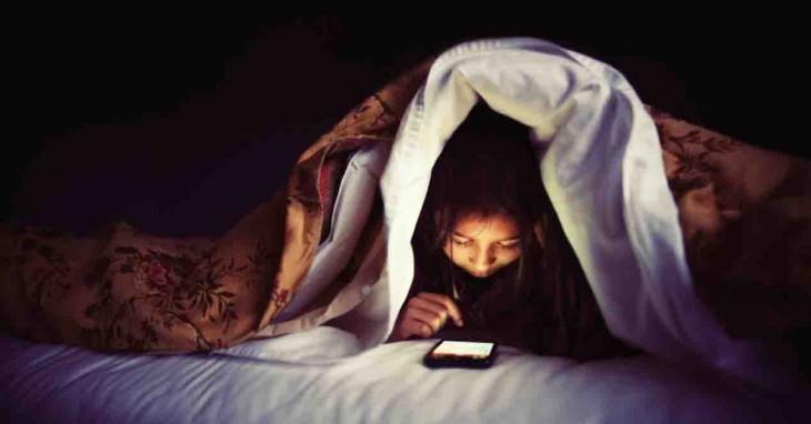 Adolescente utilizando el celular en su cuarto