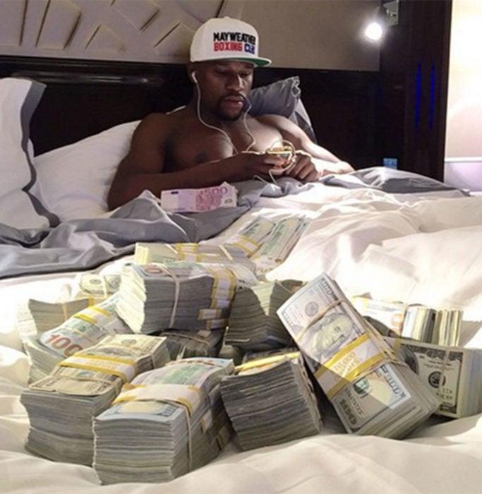 Floyd Mayweather en cama con billetes