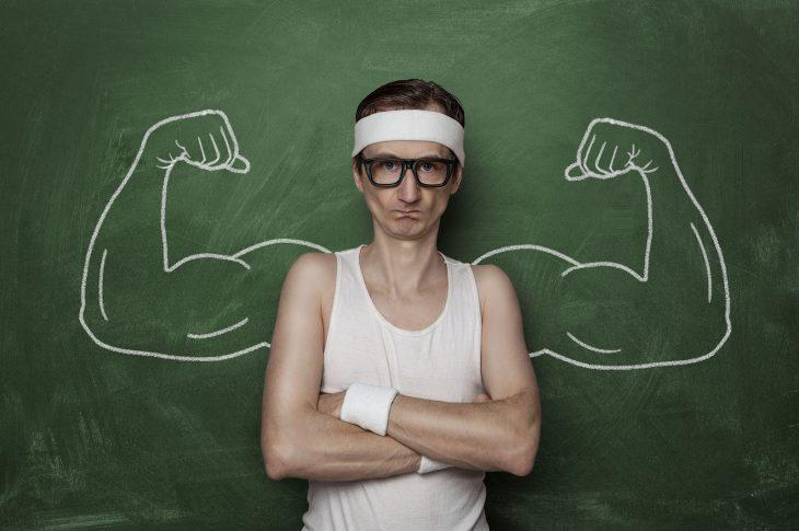 hombre delado con brazos musculosos dibujados en pizarron