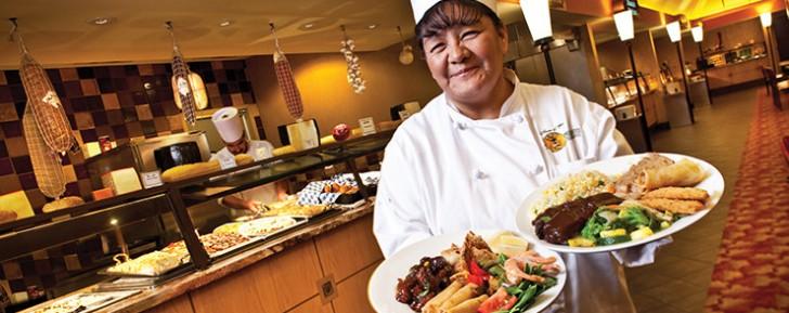 mujer cherf con dos platos de comida en la mano