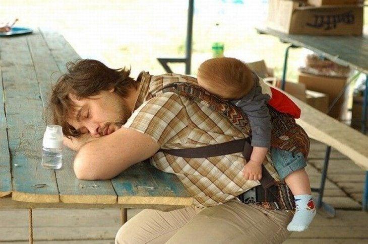 hombre dormido con bebé en la espalda