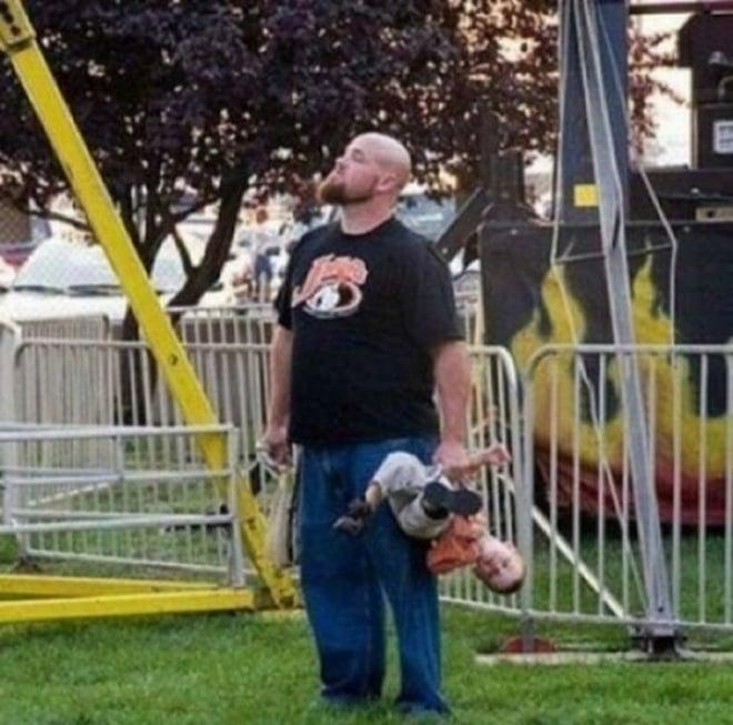 Papa cargando a niño al revés