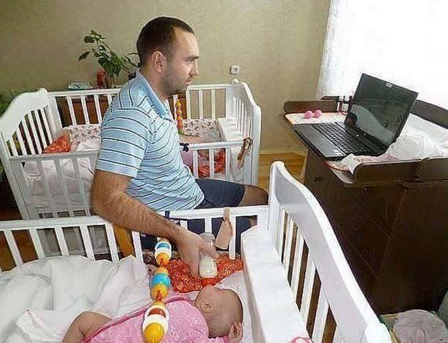 hombre en la computadora alimentando a bebé