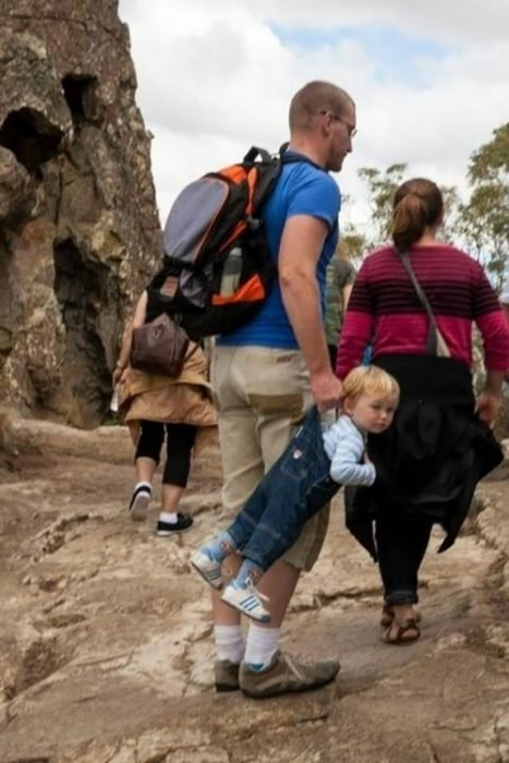 papá cargando a bebé de los tirantes con overol