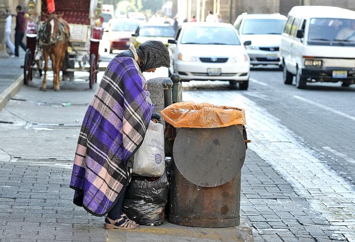 Hombre busca en la basura