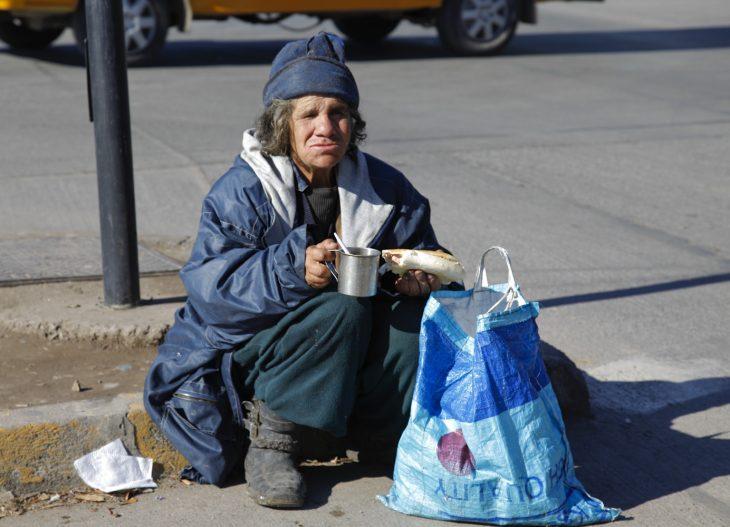 Indigente comiendo en la calle