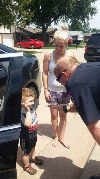 niño saludando policia