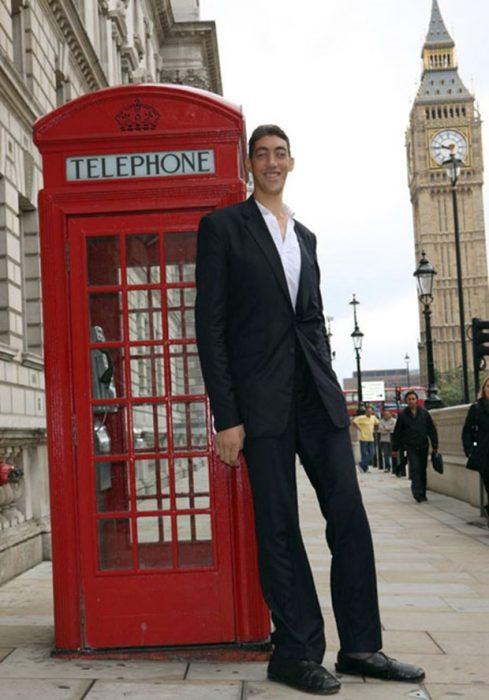 Hombre muy alto en cabina telefónica
