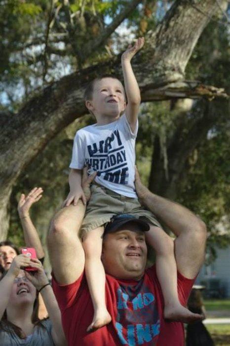Niño cargado en hombros