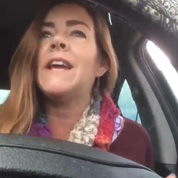 Mujer cantando en el auto