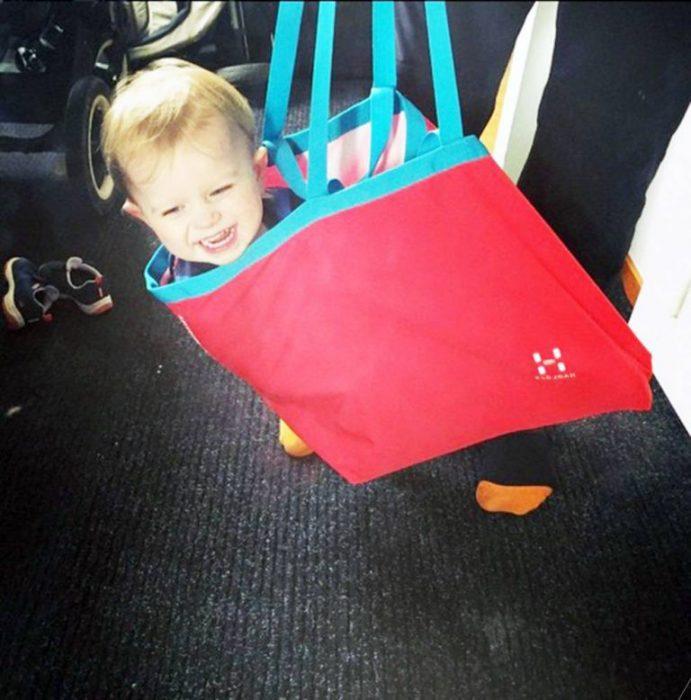 Niño cargado en una bolsa
