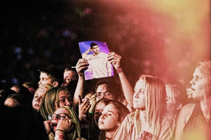 Hombre sosteniendo cartel en concierto de 1D