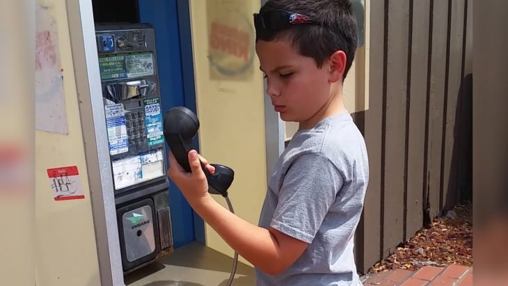 Niño confundido con teléfono de monedas