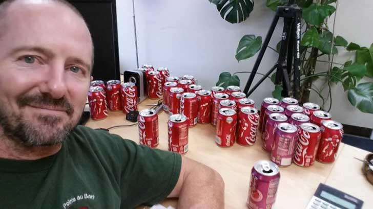 Hombre entre latas de Coca Cola