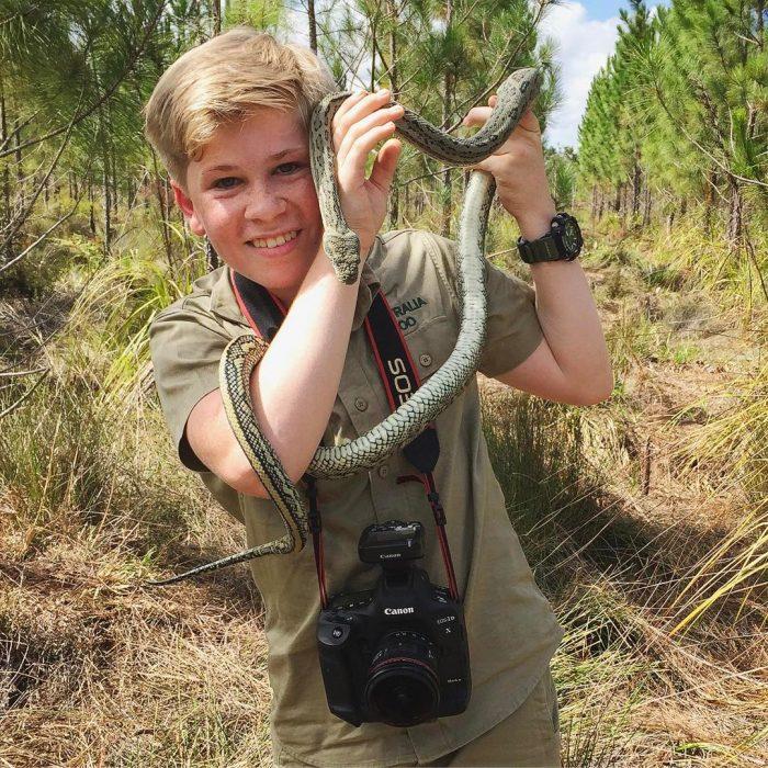Niño sostiene una serpiente