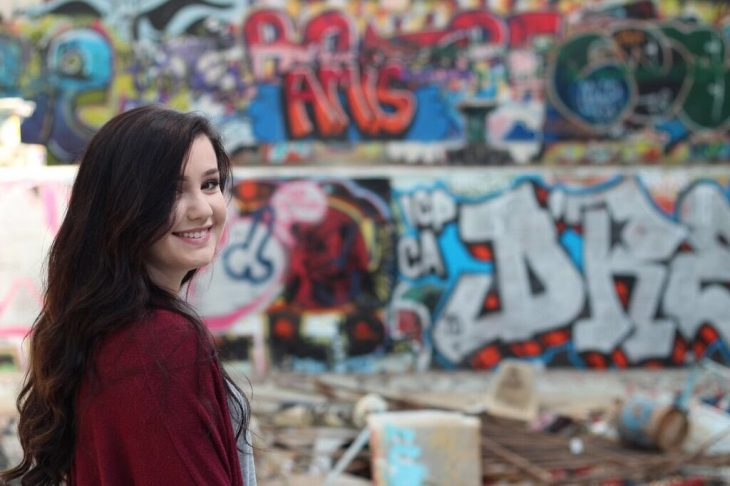 Chica sinriendo de espaldas grafiti fondo