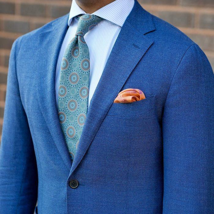 traje azul con pañuelo de color naranja