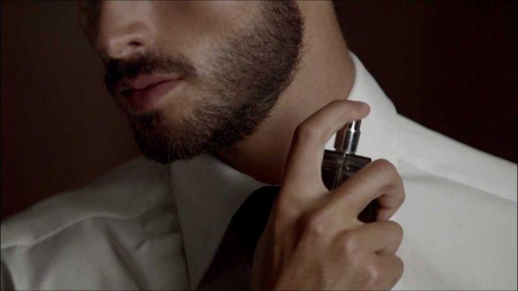 hombre aplica perfume