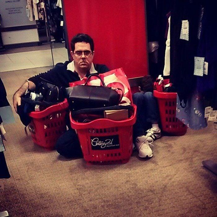 Hombres esperando a mujeres de compras