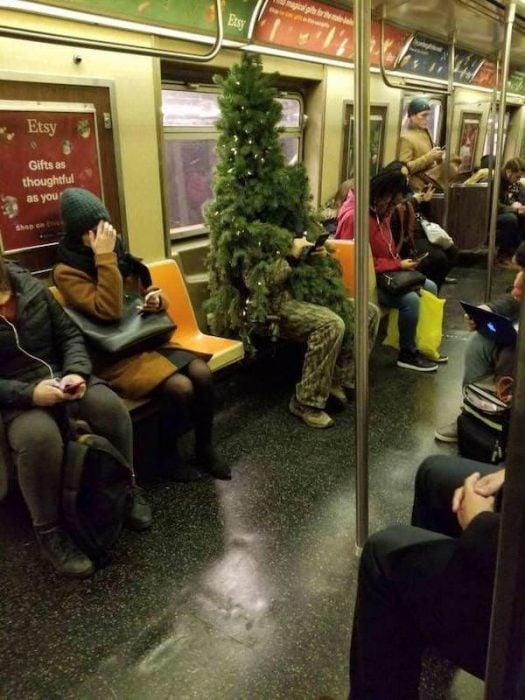 gente extraña metro arból navidad