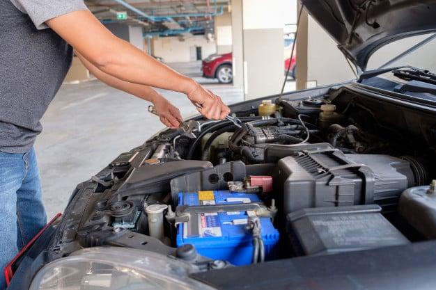 hombre arreglando un auto
